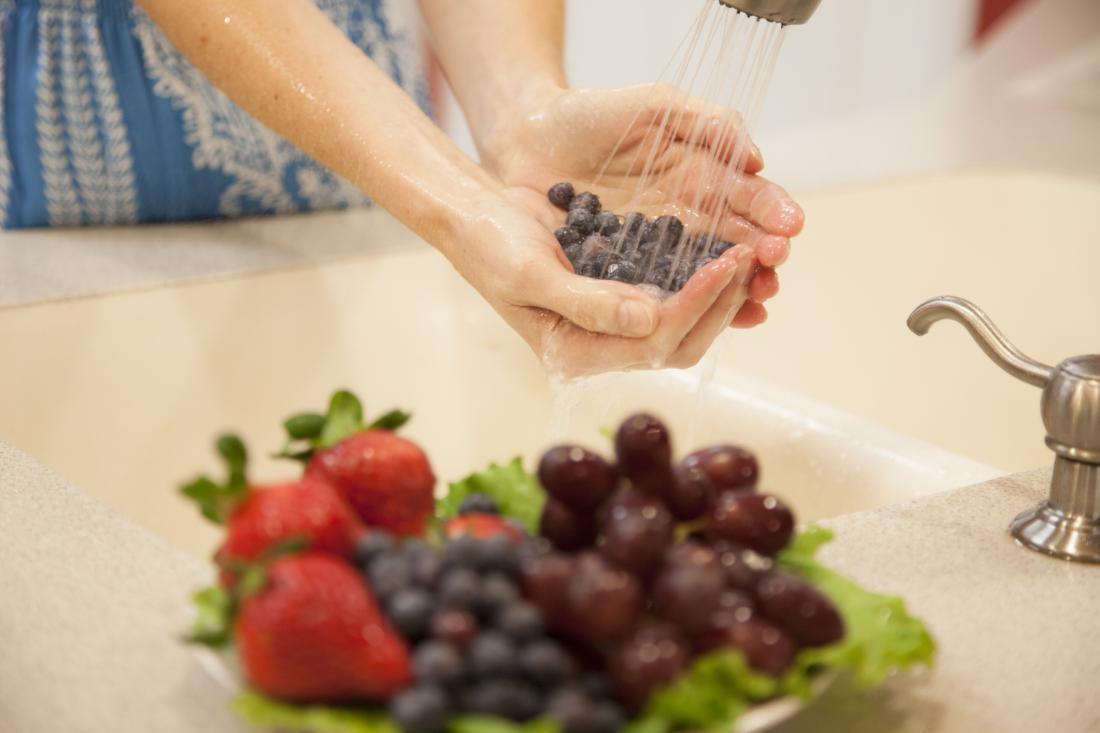 close up of woman$0027s hands washing fruit