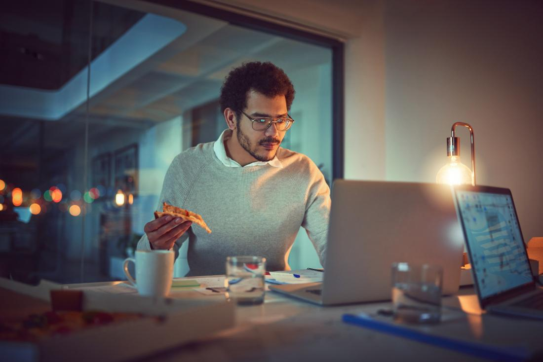 man eating pizza while working